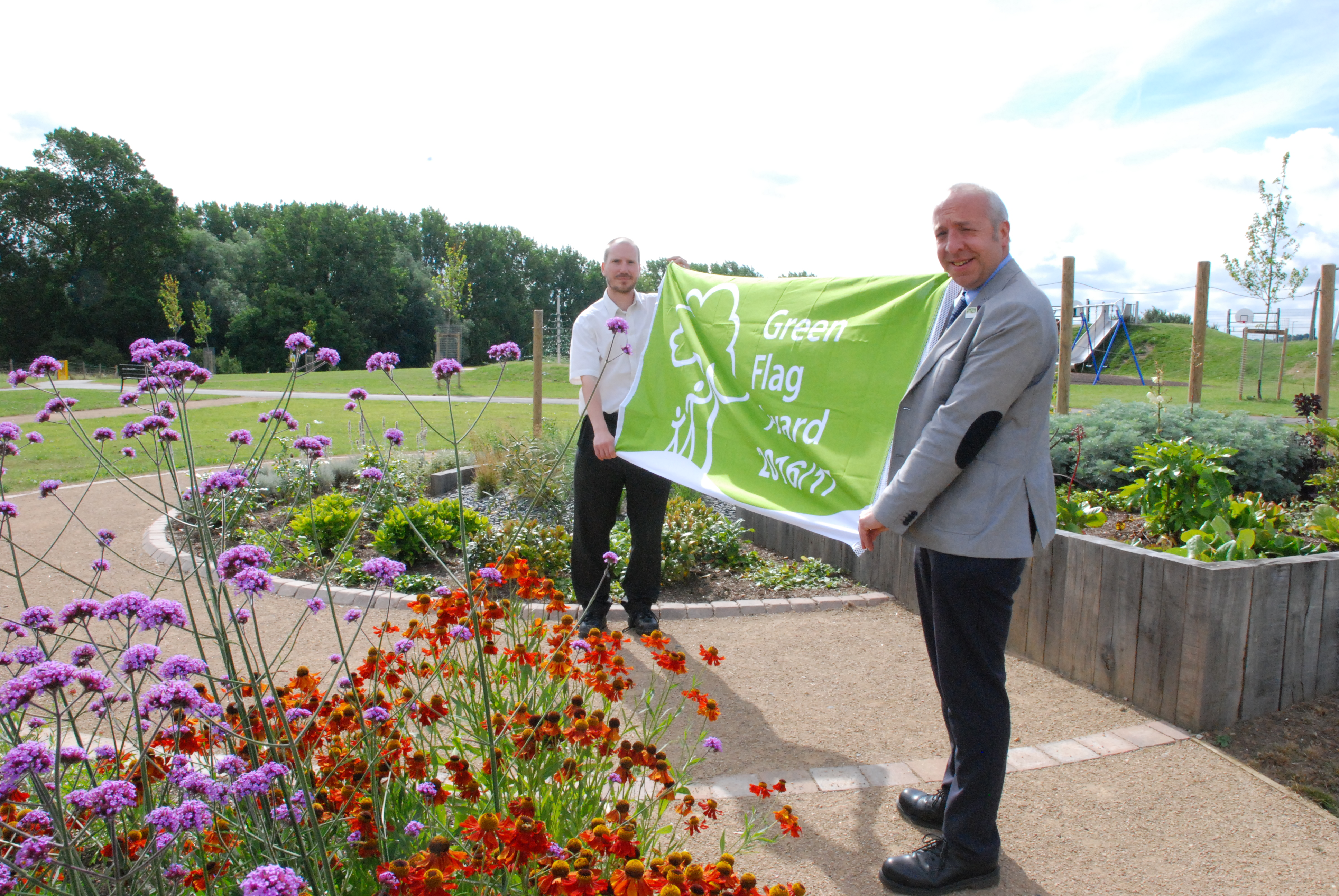 Colin Horton, Green Spaces Officer, and Chris Worman, Parks and Grounds Manager, celebrate a Green Flag Award for Centenary Park, Newbold.
