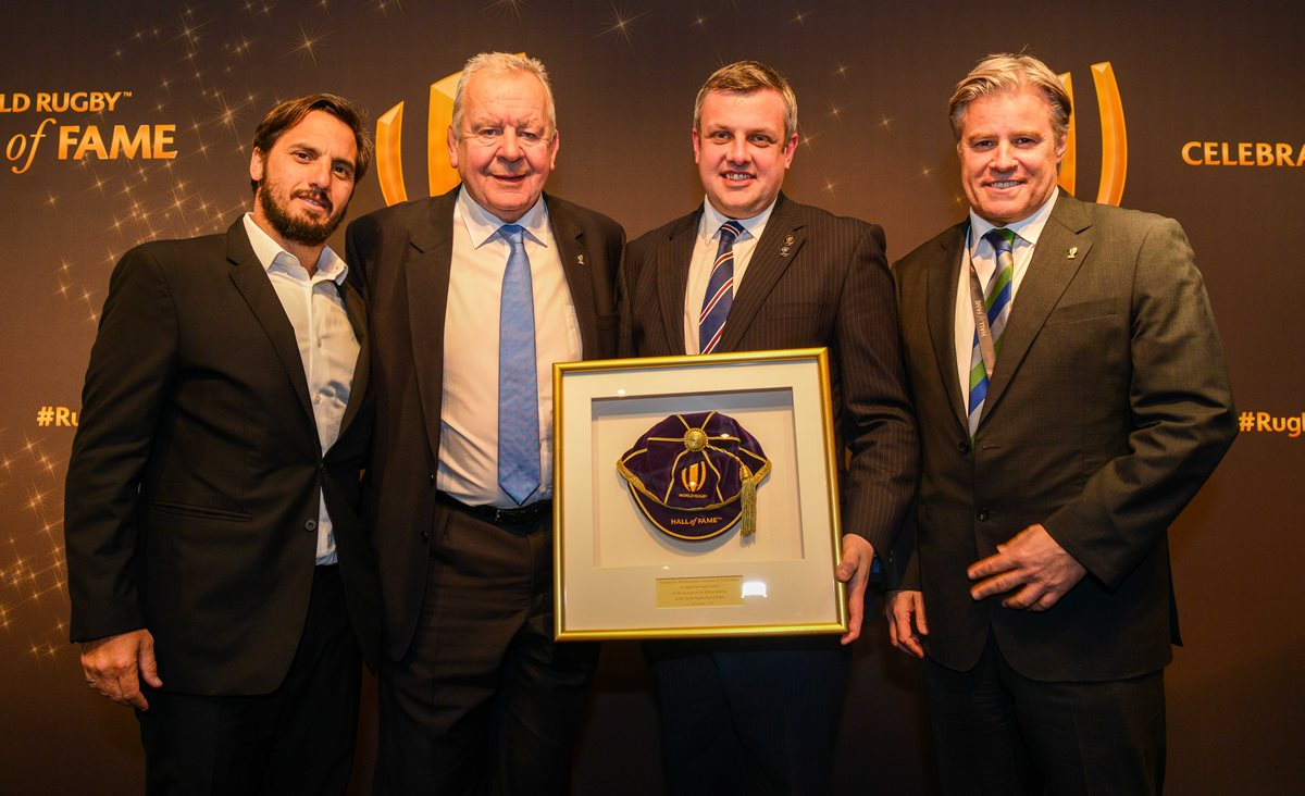 Agustin Pichot, Bill Beaumont and Brett Gosper of World Rugby, present a commemorative cap to Cllr Michael Stokes, Leader of Rugby Borough Council.